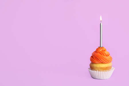 Birthday cupcake with candle on violet background, space for text