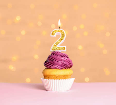 Birthday cupcake with number two candle on table against festive lights Stock fotó