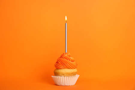 Birthday cupcake with candle on orange background Stockfoto - 128780640