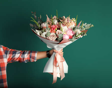 Man holding beautiful flower bouquet on green background, closeup view Stockfoto - 128780648