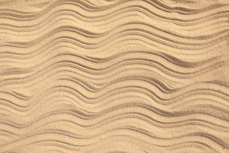 Top view of beach sand with wave pattern as background