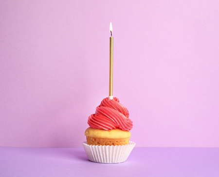 Birthday cupcake with candle on violet background