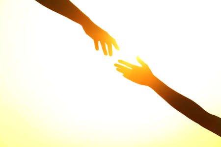 Silhouettes of man and woman helping each other against sunset, closeup