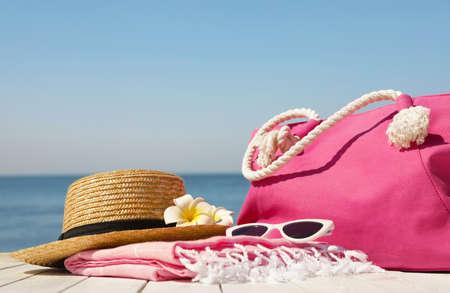 Stylish beach accessories on wooden pier near sea Фото со стока