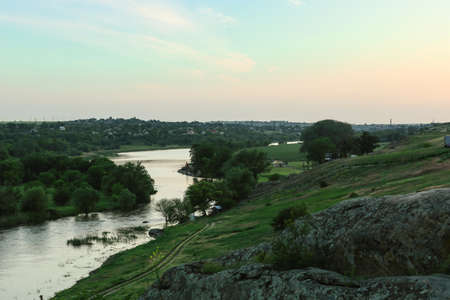 Picturesque landscape with river and green hills on summer evening Фото со стока