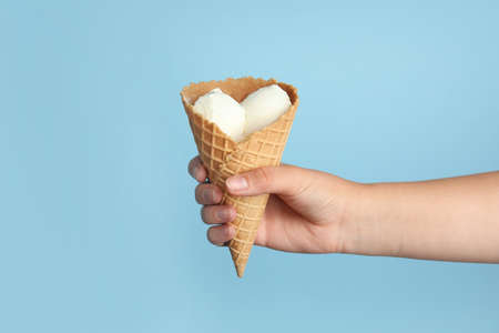 Woman holding delicious ice cream in wafer cone on blue background, closeup