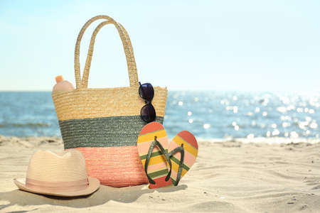 Bag and beach objects on sand near sea, space for text