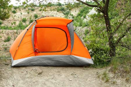 Modern camping tent near tree in wilderness
