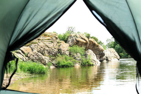 Calm river with rocky bank, view from camping tent