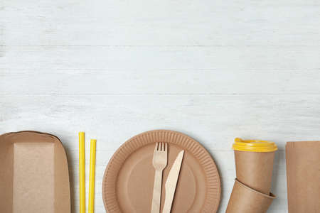 Flat lay composition with new paper dishware on white wooden background, space for text. Eco life
