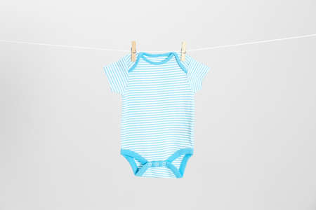 Cute baby cloth hanging on clothes line against light grey background. Laundry day
