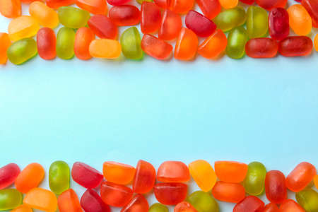 Frame of sweet jelly candies on blue background, top view. Space for text