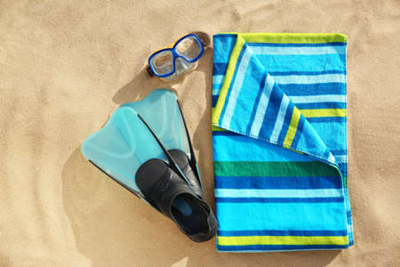 Flat lay composition of beach objects and towel on sand