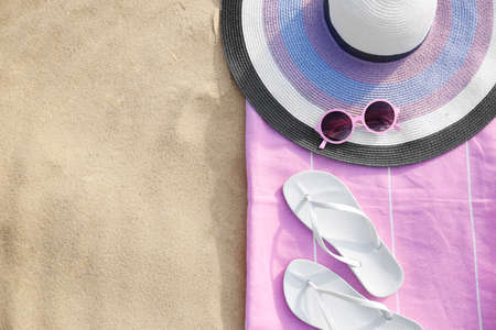 Flat lay composition of beach objects and towel on sand, space for text