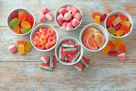 Flat lay composition with bowls of different jelly candies on wooden background Stockfoto