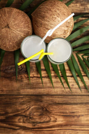 Flat lay composition with glasses of coconut water on wooden background. Space for text