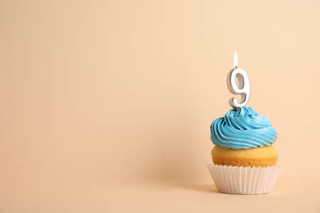 Birthday cupcake with number nine candle on beige background, space for text Stock fotó