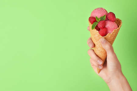 Woman holding wafer cone with delicious raspberry ice cream on green background, closeup. Space for text Stock Photo