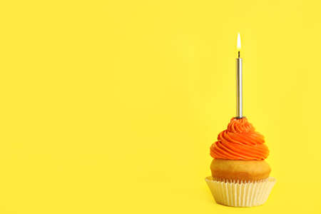 Birthday cupcake with candle on yellow background, space for text