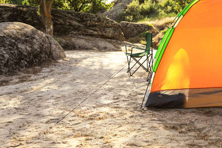 Modern camping tent and chair in wilderness. Space for text