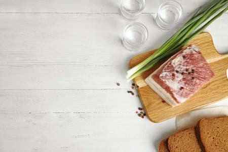 Board with pork fatback, onion, bread and shots of vodka on white wooden background, flat lay. Space for text