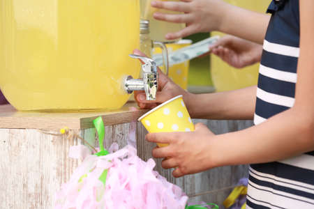 Little girl pouring natural lemonade into cup, closeup. Summer refreshing drink