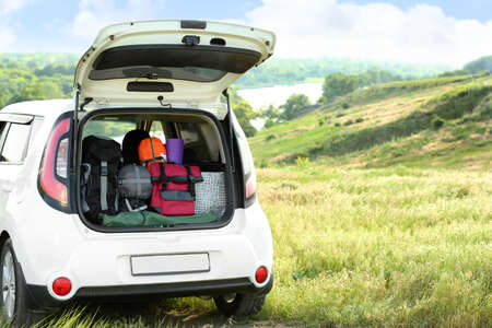 Car with camping equipment in trunk on green field. Space for text