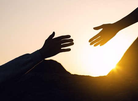 Silhouettes d'homme et de femme s'aidant à grimper sur la colline contre le coucher du soleil, gros plan