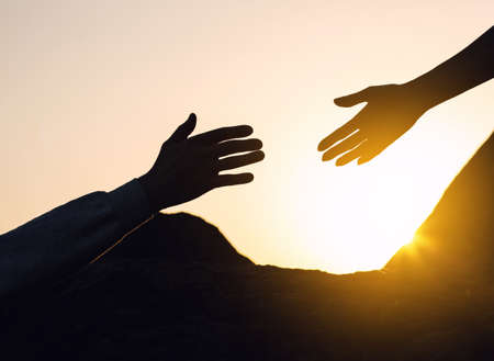 Silhouettes of man and woman helping each other to climb on hill against sunset, closeup