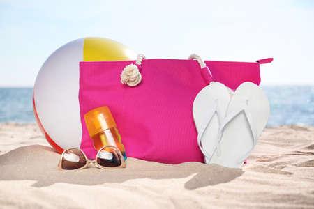 Bag and beach objects on sand near sea