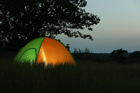 Modern tent lit from inside in wilderness at night, space for text. Overnight camping Stockfoto