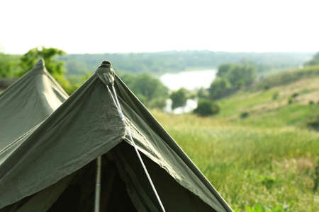Camping tent in green field on sunny day. Space for text Stockfoto