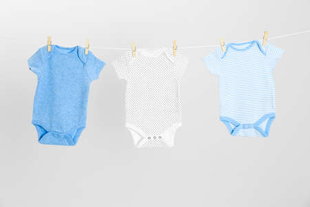 Different baby clothes hanging on clothes line against light grey background. Laundry day
