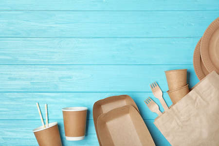 Flat lay composition with new paper dishware on blue wooden background, space for text. Eco life