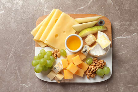Board with different kinds of delicious cheese and snacks on marble background, top view
