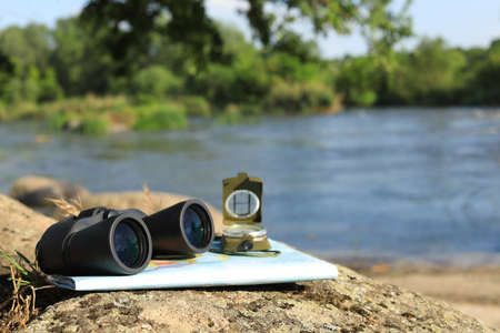 Binoculars, compass and map on stone near river, space for text. Camping equipment