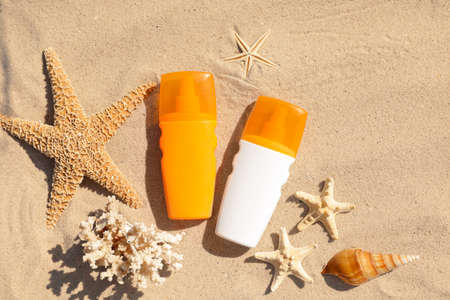 Flat lay composition with bottles of sunblock on sandy beach