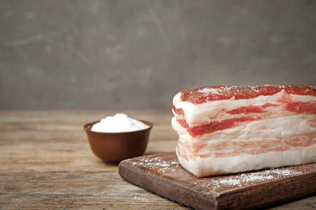 Board with bacon and salt on wooden table. Space for text