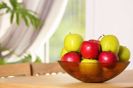 Bowl with different sweet apples on table in room, space for text Stock fotó