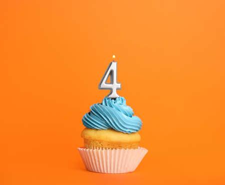 Geburtstagskuchen mit Kerze Nummer vier auf orangem Hintergrund