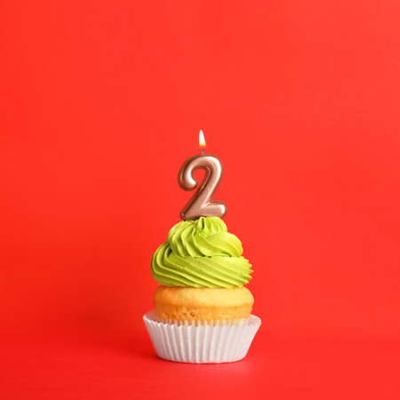 Birthday cupcake with number two candle on red background Stock fotó