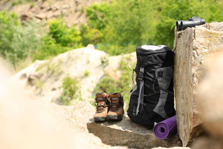 Backpack and camping equipment on rocks in wilderness. Space for text