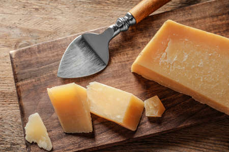 Board with cut Parmesan cheese on wooden table, top view Stock Photo - 128781287