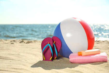 Inflatable ball and beach objects on sand near sea, space for text