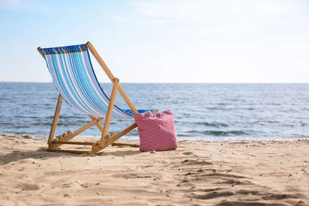 Lounger and bag on sand near sea, space for text. Beach objects