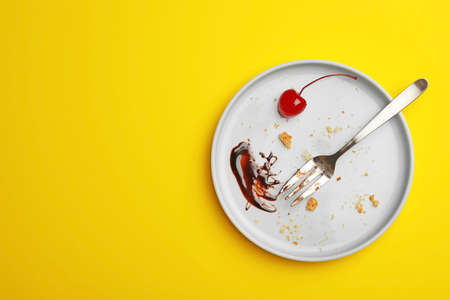 Dirty plate with food leftovers, fork and canned cherry on yellow background, top view. Space for text Imagens