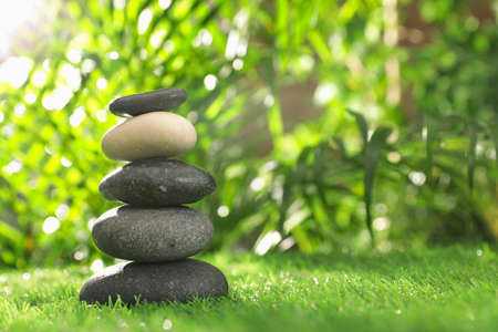 Stack of stones on green grass against blurred background, space for text. Zen concept Banco de Imagens