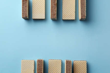 Tasty wafer sticks on blue background, flat lay with space for text. Sweet food