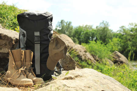 Backpack and camping equipment on large stone in wilderness. Space for text