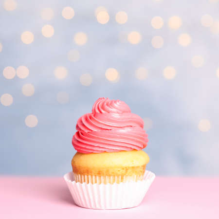 Tasty birthday cupcake with cream on table against festive lights Stock fotó